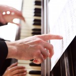 Close up of musician man and girl hands piano playing